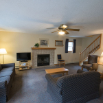 2,000 sq. ft. townhouse with 4 bedrooms - View of the living area with couch, fireplace, and staircase