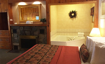 room with one guest bed and whirlpool tub