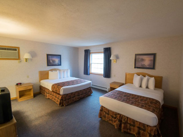 one queen bed and one full bed in the two bedroom suite
